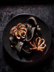 Grilled Octopus with black noodles on dark plate