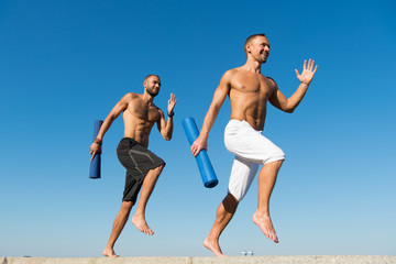 Forward to healthy lifestyle. Men with yoga mat captured in motion blue sky background. Sportsman with mat running. Run training outdoor. Runners hurry to stretch muscles after training. Yoga classes