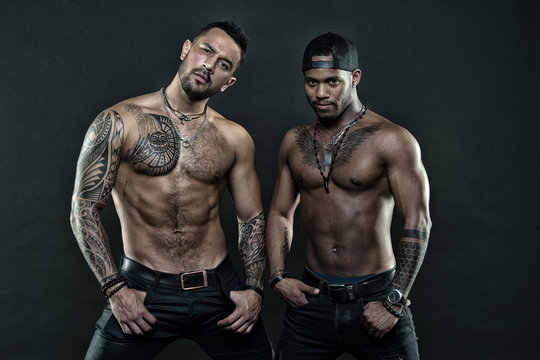 Men tattooed muscular body. Fashion models muscular chest. Sportsmen muscular belly posing. Sport and bodycare. Muscular and masculine guys look confident. African and hispanic men sexy bare torso