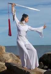 Young woman dancer with a sword on a Connecticut beach.