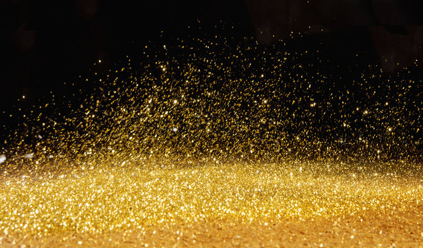 Golden powder scattered over the dark background