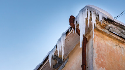 Icicles hang from roof of building. Danger for passers, threat of death and injury from icicles. Winter threats