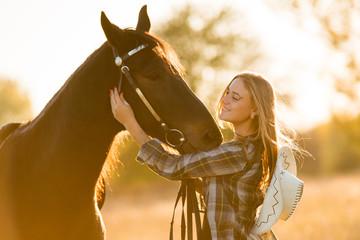 Girl equestrian rider stands near the horse. Horse farm