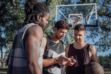Basketball Players Looking at Cell Phone