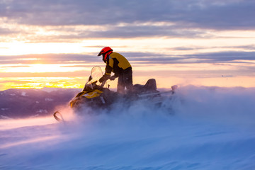 A man is ridind snowmobile in mountains. Wall mural