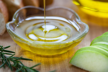 Olive oil being poured into bowl with Italian ingredients