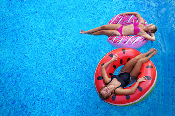 girls in bikini smimming and tanning in pool on the inflatable m
