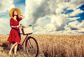 Redhead girl with bicycle on wheat field.