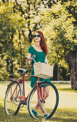 Redhead with bicycle in the park. Summertime season