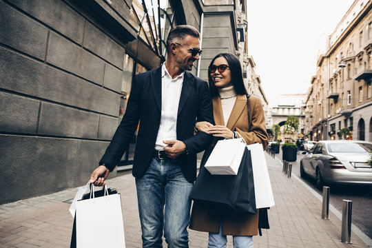 Shopping. Black Friday. Couple. Love. Man and woman with shopping bags are smiling while walking down the street