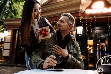 Couple. Holiday. Cafe. Woman is giving a gift box to her man. Both are in warm casual clothes smiling while sitting in the cafe outdoors