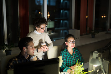 Group of three young people working in dark office late at night, copy space