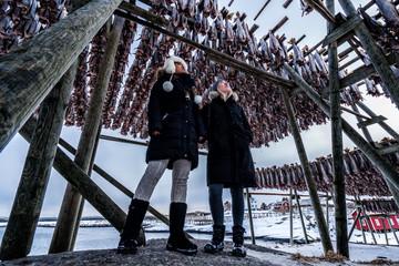 Women tourists admiring the racks of cod fish in Reine, Norway.  Lofoten Islands