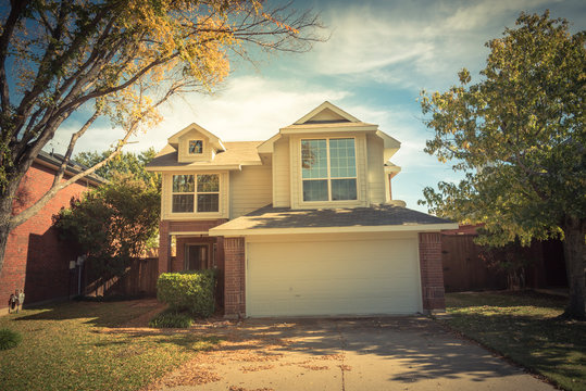 Vintage tone single-detached dwelling home in suburban Dallas-Fort Worth with attached garage. Colorful autumn fall foliage in North America.