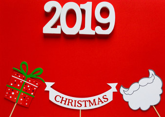 numbers 2019 and photo booth colorful props for christmas party - beard, santa claus, gift on red background. Christmas and New year decorations