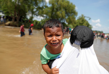 A boy, traveling to the U.S. with a caravan of migrants, cries as he is being helped to the shore after crossing with others the Suchiate river, a natural border between Guatemala and Mexico, in Ciudad Hidalgo