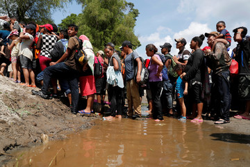 Migrants, part of a caravan traveling to the U.S., stand in line to climb a little hill after crossing the Suchiate river, a natural border between Guatemala and Mexico, in Ciudad Hidalgo