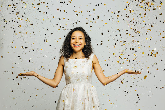 Celebrate life, portrait of a smiling woman with arms out and golden confetti falling