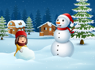 A girl making snowman in winter and snowy landscape