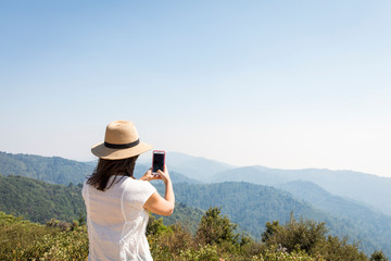 Woman taking photo from top of mountain