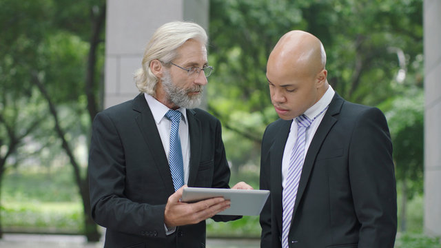 corporate executives discussing business using digital tablet