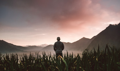 silhouetted man standing on the field in sunset with mountain background Wall mural