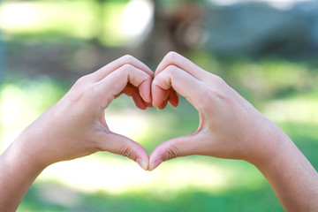 human hands doing heart symbol on nature background.