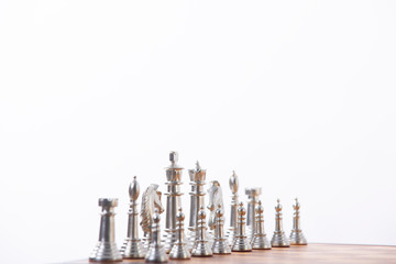 Gold and silver chess pieces on a wooden chess board