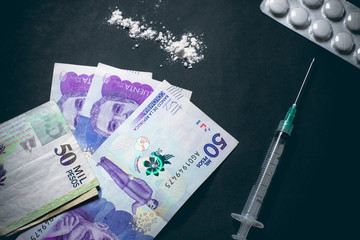 Cocaine, drugs and colombian pesos on a dark background