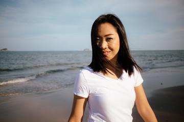Happy woman enjoy the sunset light on the beach.