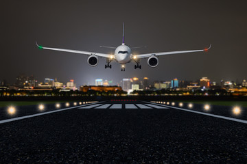 Airplane take off / landing at night with blurred town on background Wall mural