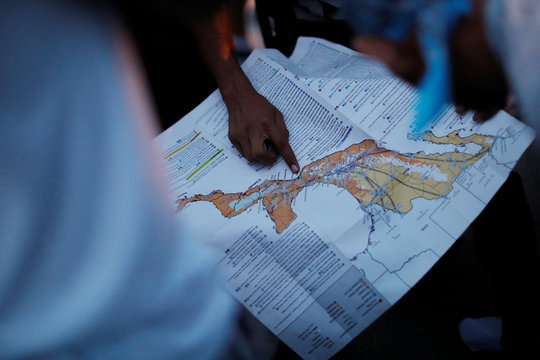 A migrant, part of a caravan of thousands traveling from Central America en route to the United States, points at a map while rest in Santiago Niltepec