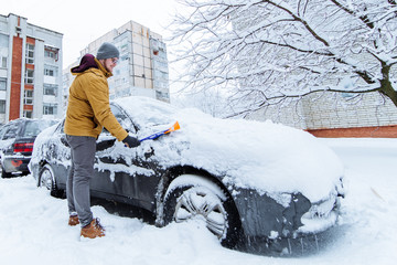 man cleaning car after snowstorm