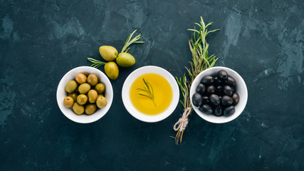 A set of olives and olive oil and rosemary. Green olives and black olives. On a black stone background. Free space for text. Wall mural