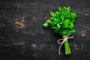 Fototapete - Fresh parsley. Top view. On a black wooden background. Free space for text.