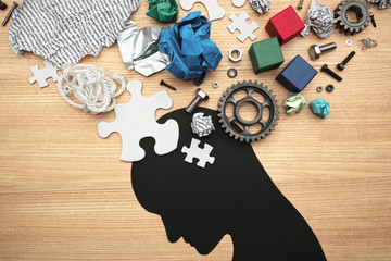 Concept image of mental exhaustion and brain fatigue. Concentration problems. various parts and head silhouette on wood background.
