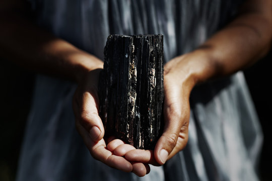 Woman's hands holding dark, powerful black tourmaline crystal in healing concept