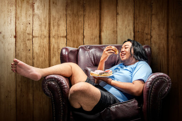 Asian fat man eating donuts on plate