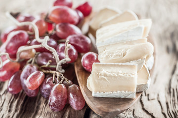 Organic homemade white brie cheese with pink grapes on a wooden Board