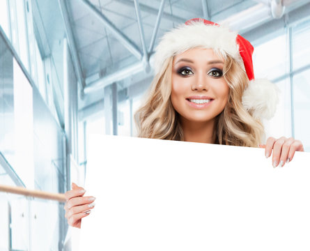 Happy business woman in Santa hat with white empty paper board banner background with copy space