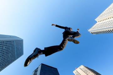 ビル街を青空バックにジャンプするスーツ姿のビジネスマン1人。挑戦,努力,成功,元気イメージ