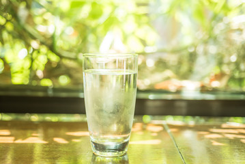 Cold glass of water on wooden table