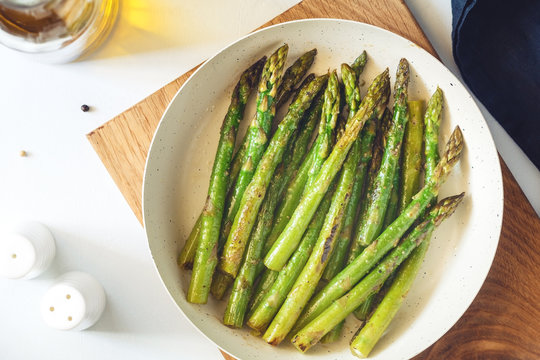 Top view on roasted asparagus in a white pan on a kitchen table. Modern style, vegetarian food.