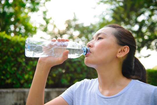 Asian woman drinking water after exercise at the park
