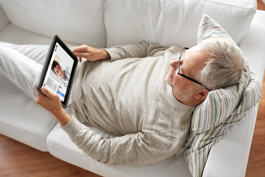 medicine, technology and healthcare concept - senior patient having video chat with doctor on tablet pc computer at home
