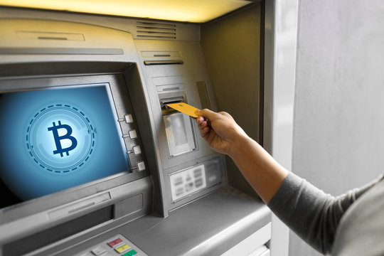 finance, cryptocurrency and technology concept - close up of woman hand inserting bank card to atm machine with bitcoin icon on screen
