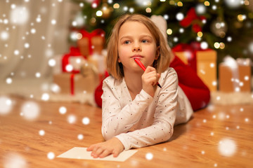 christmas, holidays and childhood concept - girl writing wish list or letter to santa at home