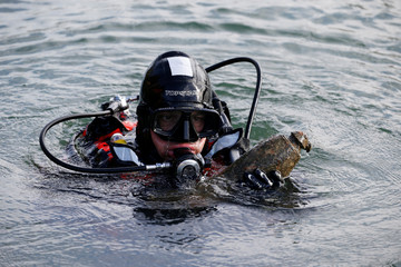 A diver from a bomb-disposal unit gies up the surface an unexploded shell recovered in the Meuse River at Sivry-sur-Meuse, close to WWI battlefields