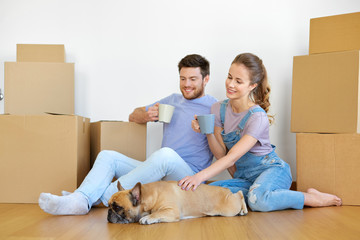 mortgage, people and real estate concept - happy couple with boxes and french bulldog dog moving to new home and drinking coffee Wall mural