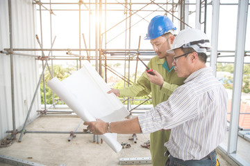 engineer people working and discussing with architecture or blueprint at construction site